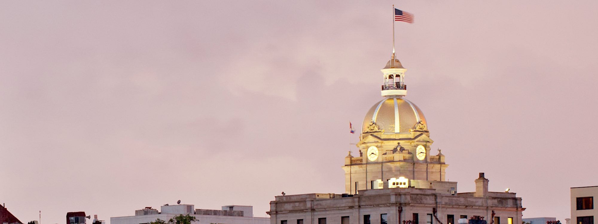 Savannah, GA's City Hall dome stands against the pink sky at sunset.