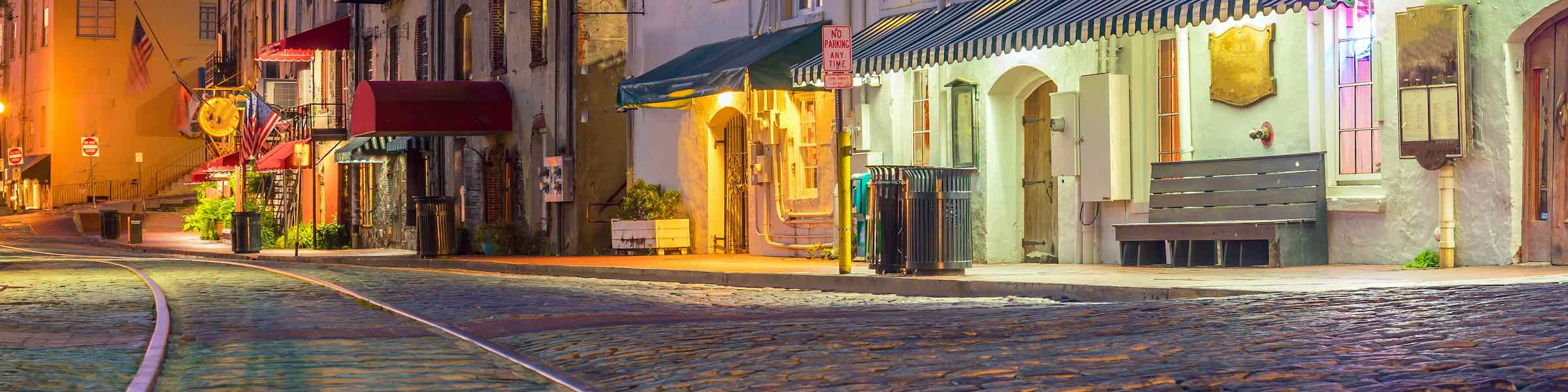 Night view of streetcar tracks on Savannah, GA's cobbled River Street, with illuminated shops and restaurants.