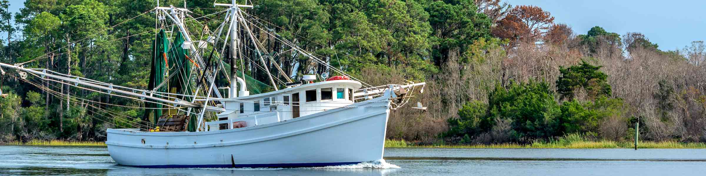 A shrimp boat sailing down a lowcountry river.