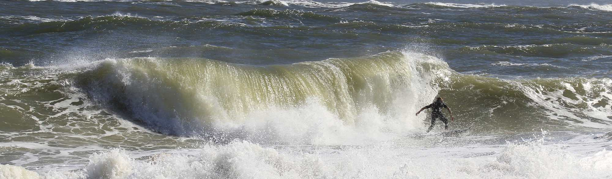 Large wave behind a surfer.