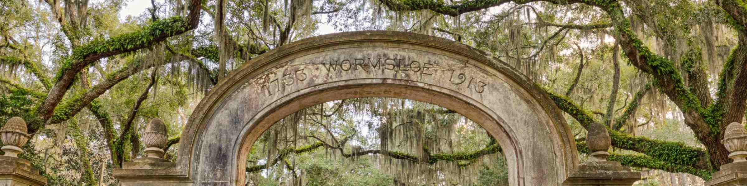 Mossy live oaks behind the gateway arch of Savannah's colonial-era plantation, Wormsloe.